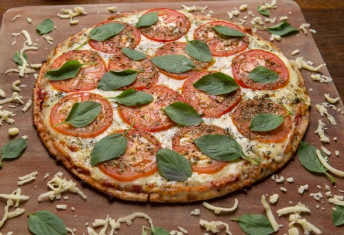 As pizzas da casa, servidas à xadrez, na tábua, utilizam uma receita exclusiva com ingredientes que deixam a massa mais leve e crocante. (Foto: Tiago Trindade/divulgação)