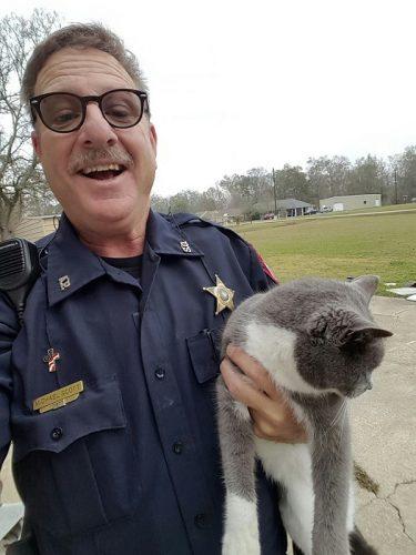 O policial com a gata Bella (foto: reprodução/Facebook).