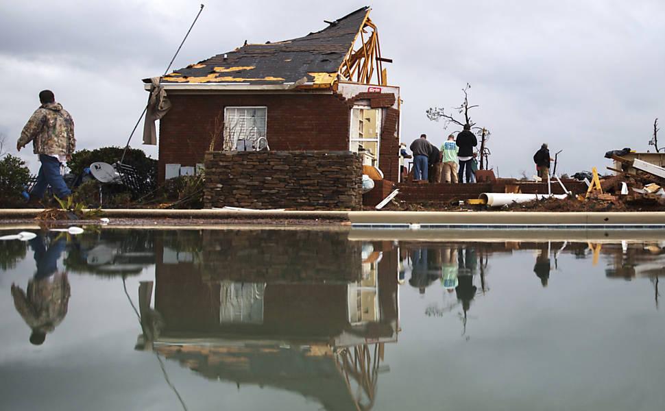 Moradores trabalham para limpar área de casa destruída por tornado na cidade de Adel, na Geórgia (Foto: AP)