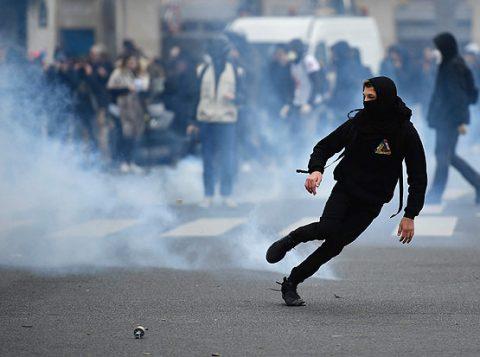 Jovem foge de gás lacrimogêneo em protesto em Paris na quinta. (Foto: Reprodução)