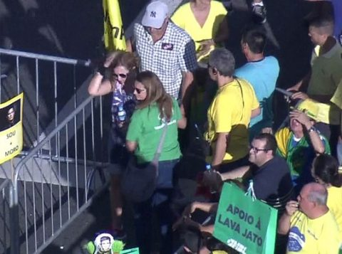 Mulher de camisa azul deixa a avenida Paulista com a mão na cabeça após ser atingida por um drone. (Foto: Reprodução)